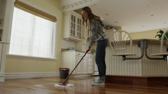 "vídeos de stock e filmes b-roll de ""low angle medium panning shot of woman mopping kitchen floor / cedar hills, utah, united states"" - balde"