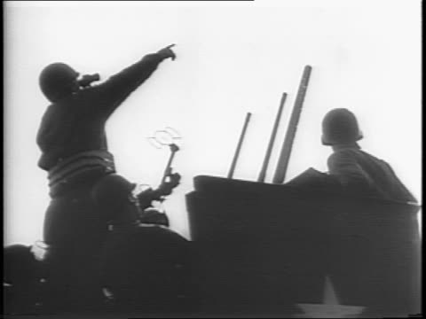 Low angle medium shadow shot of soldiers on rotating massive gunner as one soldier points to the sky with the cannon facing up / Medium shot of tank...