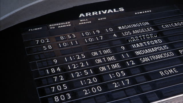 Low angle medium shot airplane flight arrivals board w/flight information changing / LAX airport