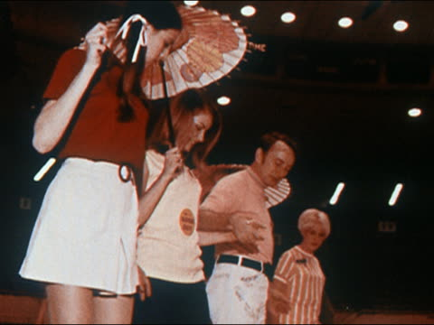 vidéos et rushes de 1970 low angle medium shot america's jr miss contestants holding parasols and practicing choreography on stage - homme dans un groupe de femmes