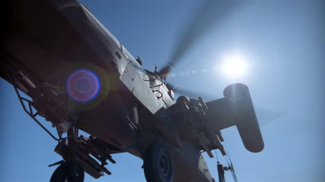 low angle medium shot apache helicopter taking off / sun shining brightly overhead / california - military helicopter stock videos and b-roll footage