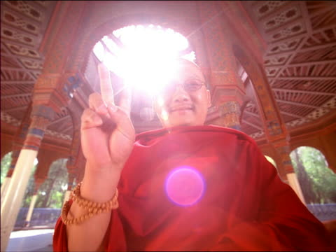 low angle medium shot asian male monk giving peace sign to camera with sun flare in open air temple / mexico city - one mid adult man only stock videos & royalty-free footage