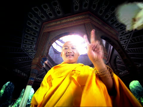 low angle medium shot asian male monk giving peace sign to camera with doves flying in open air temple in background / mexico - one mid adult man only stock videos & royalty-free footage