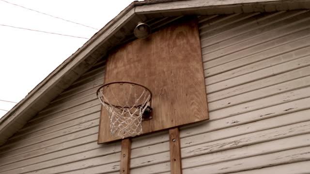 low angle medium shot basketball being shot at hoop over garage - basketball hoop stock videos & royalty-free footage