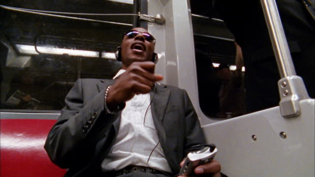 low angle medium shot black commuter singing and listening to headphones on train - mp3 player stock videos & royalty-free footage