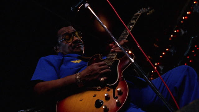low angle medium shot black man playing guitar onstage - guitarist stock videos & royalty-free footage