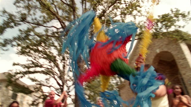 low angle medium shot blindfolded girl swinging wildly at pinata / family members gathered around watching - papier stock videos & royalty-free footage