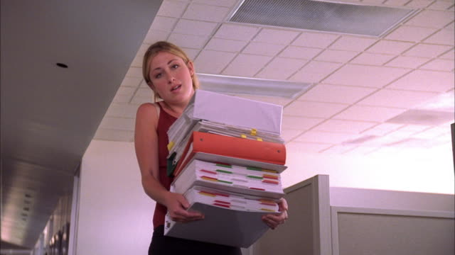 low angle medium shot blonde woman holding stack of binders and smiling at cam - akte stock-videos und b-roll-filmmaterial