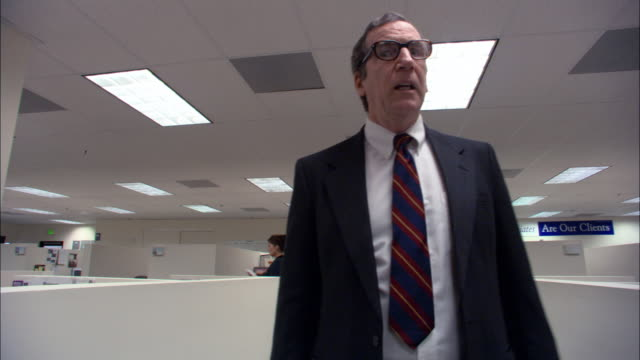 Low angle medium shot boss walking through office and looking exasperated / female employee walking by + waving / low angle