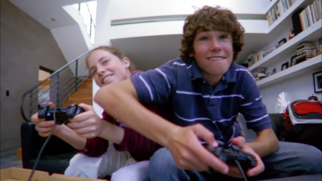 low angle medium shot boy and girl playing home video game in living room + nudging each other - games console stock videos & royalty-free footage