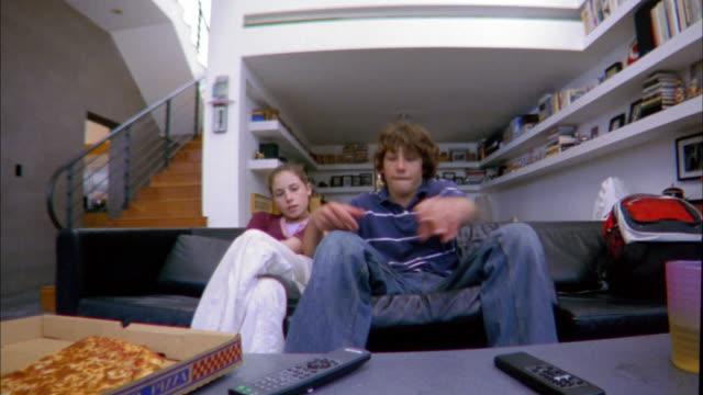 low angle medium shot boy and girl sitting on sofa + fighting for remote control - 16歳から17歳点の映像素材/bロール