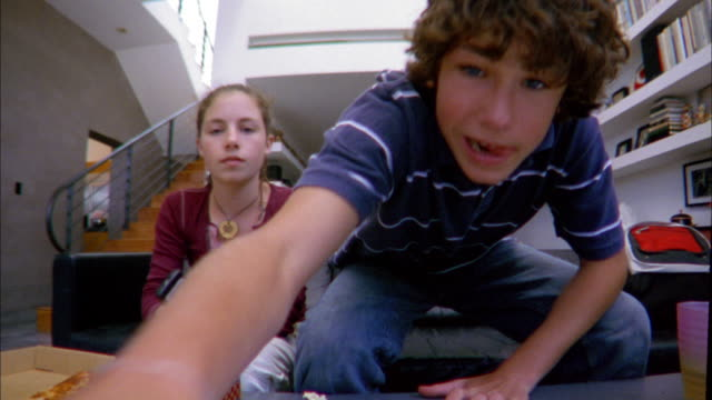 stockvideo's en b-roll-footage met low angle medium shot boy putting dvd into player / putting arm around girl and watching from sofa - dvd