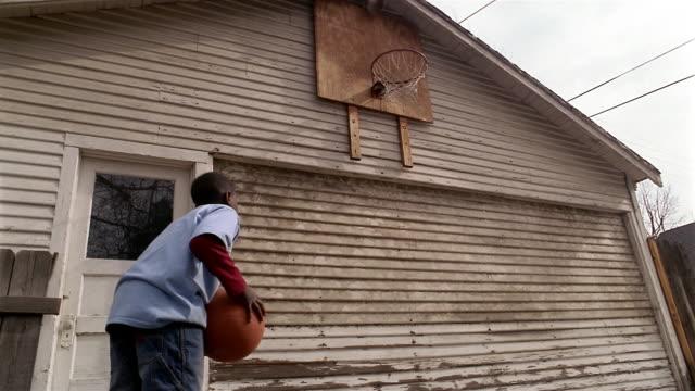 Low angle medium shot boy shooting basketball at hoop over garage