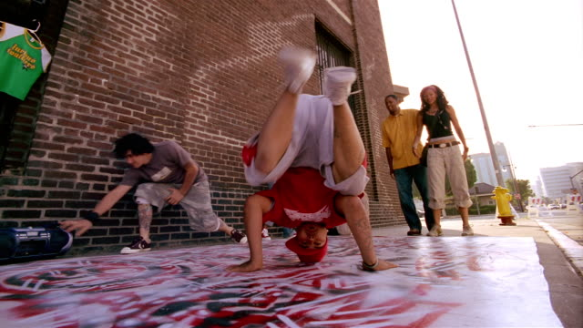 Low angle medium shot breakdancers performing on graffiti surface / looking at CAM / Los Angeles, CA