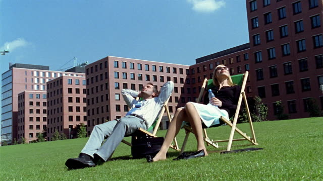 low angle medium shot businessman and woman sit on lounge chair on grass / berlin - sonnenbaden stock-videos und b-roll-filmmaterial