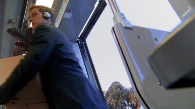 Low angle medium shot businessman boarding bus wearing headphones and carrying large plant / others boarding bus