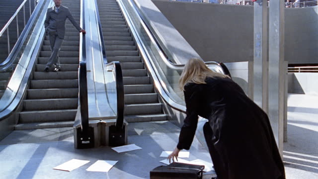 Low angle medium shot businessman coming down escalator/ zoom in woman dropping papers and man walking by rudely