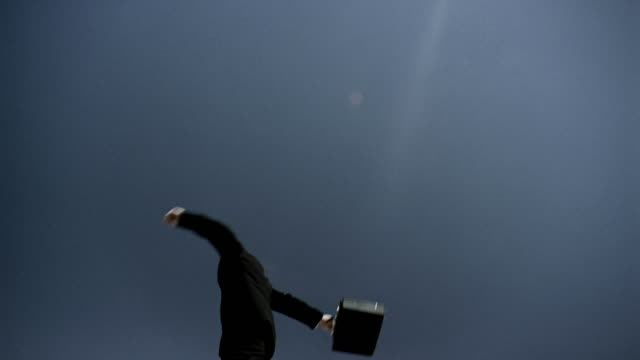low angle medium shot businessman spinning around and throwing briefcase with blue sky in background / raising his arms - briefcase stock videos & royalty-free footage