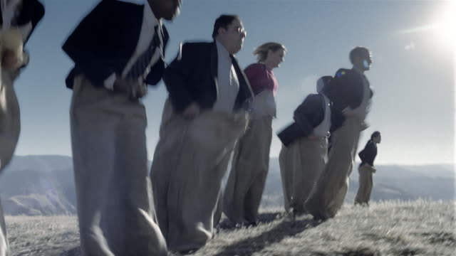 low angle medium shot businesspeople hopping through field in sack race - sack race stock videos & royalty-free footage