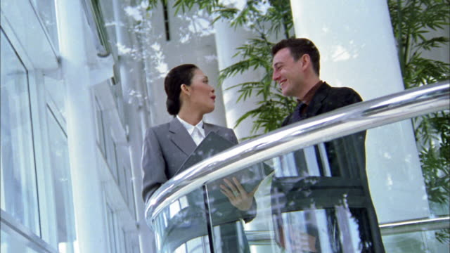 low angle medium shot businesswoman talkling to businessman on office balcony - south east asian ethnicity stock videos and b-roll footage