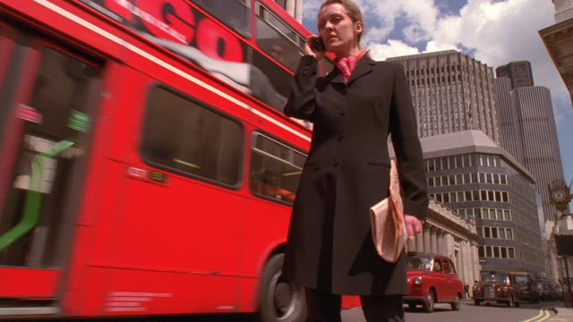 low angle medium shot businesswoman using cell phone on street with double-decker bus passing in background / london, england - folded paper stock videos and b-roll footage