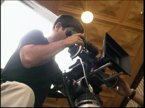 Low angle medium shot cameraman filming as person pushes camera dolly indoors