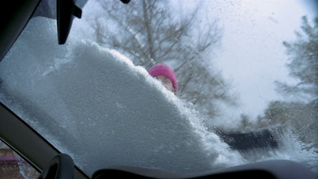 Low angle medium shot car point of view woman brushing snow off windshield of car / scraping / Vermont