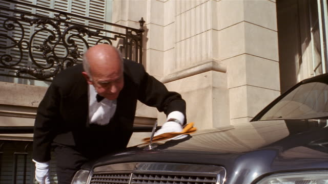 Low angle medium shot chauffeur polishing hood of limousine