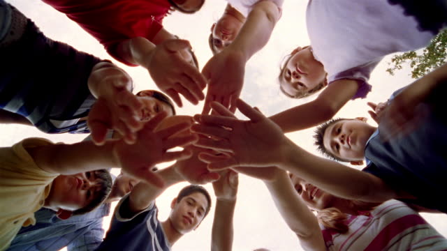 Low angle medium shot children standing in a circle with hands together / raising hands and smiling
