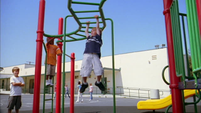 Low angle medium shot children swinging on monkey bars on playground