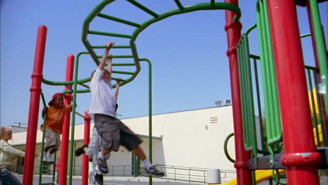 Low angle medium shot children swinging on playground monkey bars