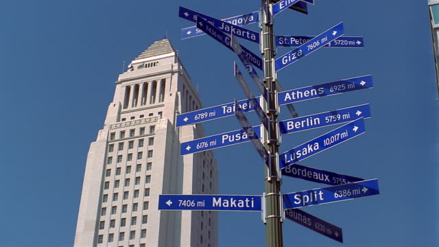 vidéos et rushes de low angle medium shot city hall building and road signs pointing in different directions / los angeles - montrer la voie