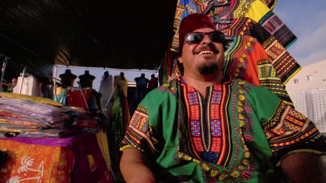 vídeos de stock, filmes e b-roll de low angle medium shot clothing vendor in sunglasses and fez laughing while sitting in market stall / venice beach, ca - kelly mason videos