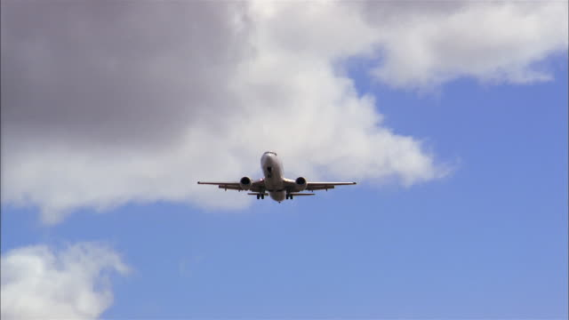 low angle medium shot commercial jet flying overhead through blue skies - low angle view stock videos & royalty-free footage
