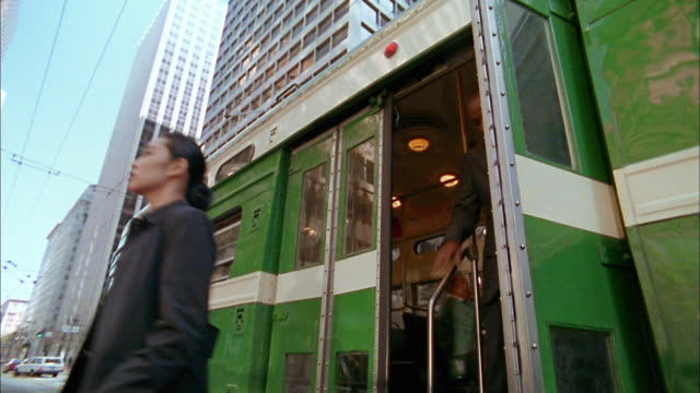 Low angle medium shot commuters getting off bus / San Francisco