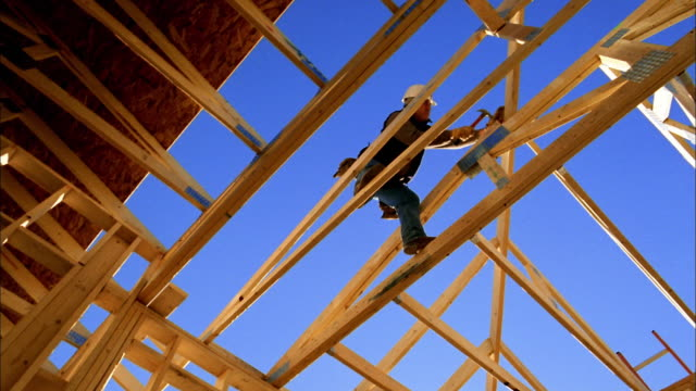 vídeos y material grabado en eventos de stock de low angle medium shot construction worker hammering on house frame / blue sky in background / phoenix, arizona - un solo hombre maduro