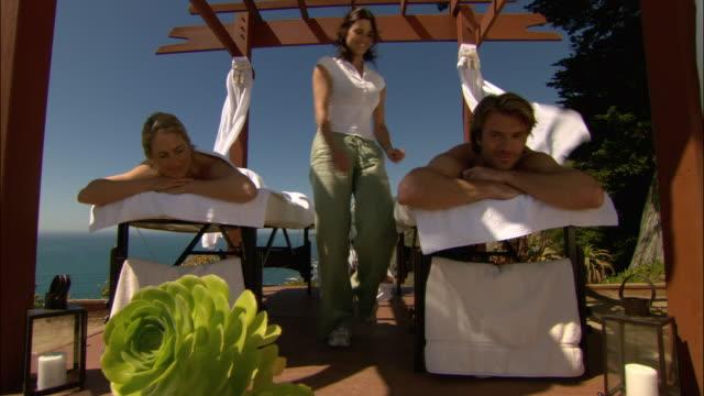 low angle medium shot couple getting massage outdoors/ monterey county, california - massagetisch stock-videos und b-roll-filmmaterial