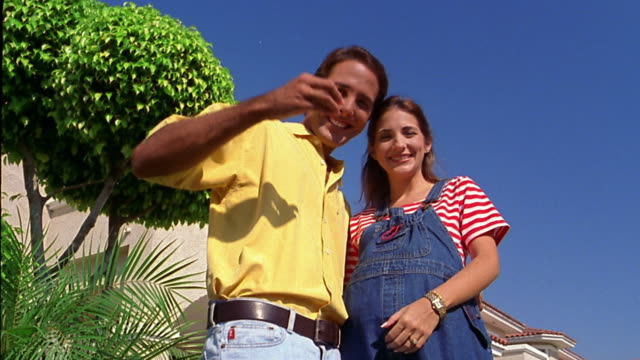 Low angle medium shot couple posing in front of house with house keys and Spanish sold sign / woman is pregnant