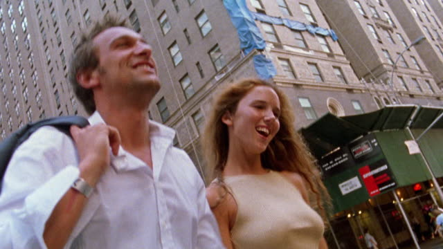 vidéos et rushes de low angle medium shot couple walking across street / nyc - samedi