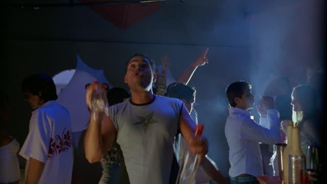 vídeos de stock e filmes b-roll de low angle medium shot crane shot bartender juggling bottles at nightclub / people dancing in background / panama - water bottle