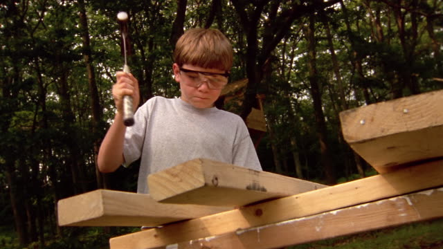 Low angle medium shot crane shot boy wearing goggles hammering nail into piece of wood