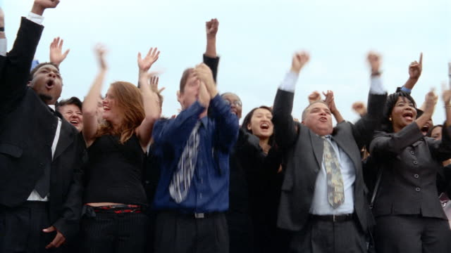 vidéos et rushes de low angle medium shot crowd of businesspeople cheering, clapping and jumping up + down - euphorique
