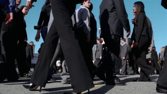 low angle medium shot crowd of businesspeople walking back and forth - 通過する点の映像素材/bロール