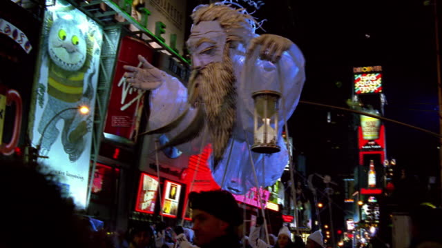 low angle medium shot crowd of people carrying large father time puppet in times square on new year's eve / new york city - beenden stock-videos und b-roll-filmmaterial