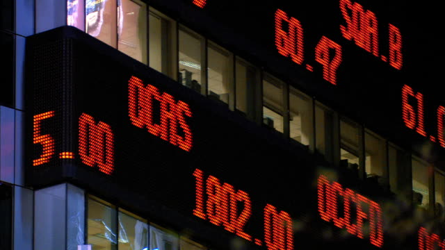 low angle medium shot digital stock ticker board on side of building / nyc - 株価点の映像素材/bロール