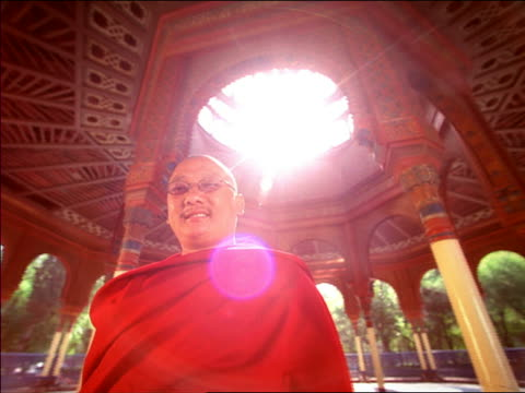 low angle medium shot dolly shot asian male monk giving peace sign to camera with sun flare in open air temple / mexico city - one mid adult man only stock videos & royalty-free footage