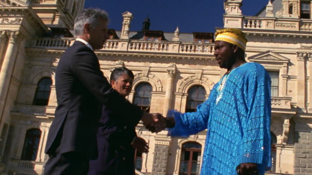 Low angle medium shot dolly shot businesswoman and two businessmen shaking hands / City Hall in background / Cape Town, South Africa