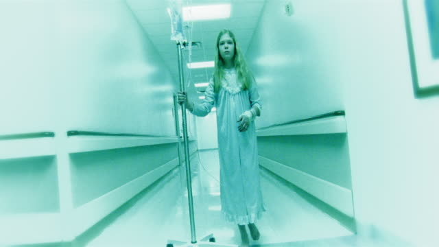 Low angle medium shot dolly shot girl walking in hospital hallway pushing her IV drip