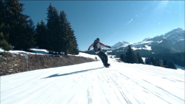 low angle medium shot dolly shot tracking shot man snowboarding downhill past pine trees - mitten stock videos & royalty-free footage