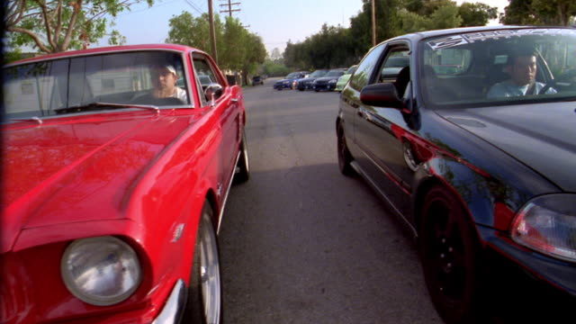 low angle medium shot dolly shot two cars w/male driver's parked next to each other / man starting street race / california - ford mustang stock videos and b-roll footage